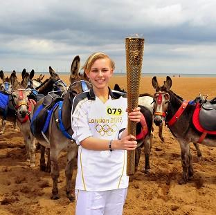 Starr Halley holds the Olympic Flame on Skegness Beach on Day 40 of the Torch Relay