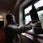 A member of a mosque in Gillingham, Kent, boards up a smashed window after a man remains in police custody on suspicion of racially-aggravated criminal damage