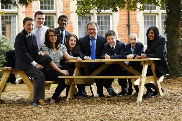 Headteacher Stephen Drew surrounded by staff and pupils celebrating their good Ofsted report