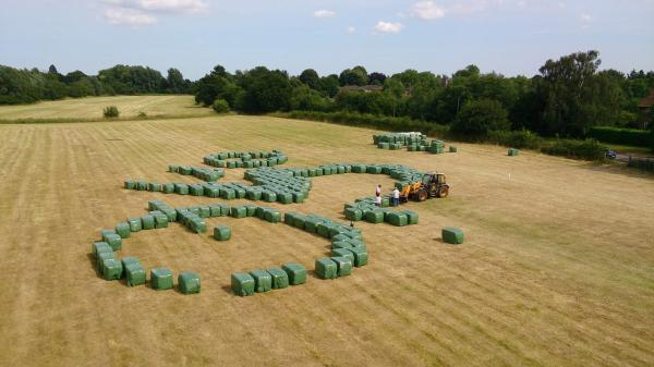 Big job! The team putting together the bales of hay to form the cyclist in the field sculpture
